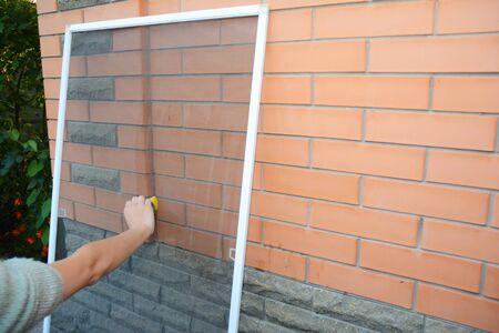 Photo pour Woman cleaning mosquito net screen from dust - image libre de droit