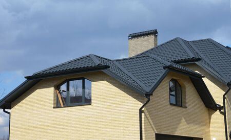 Photo pour Valley and gable house ceramic tiled roofing construction with gutter pipeline. Brick house with problem gable roof roofing construction and roof gutter pipeline system. - image libre de droit