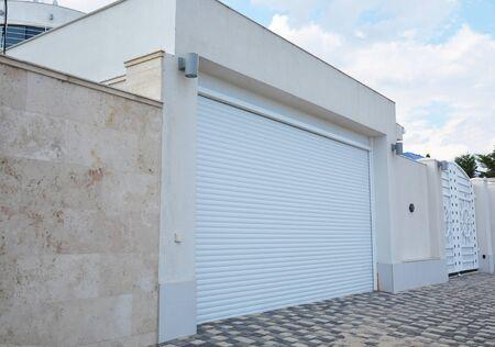 Foto de A close-up on a modern garage for cars with white garage door and lightning lamps. - Imagen libre de derechos