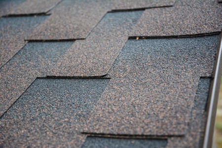 Photo pour A close-up on architectural asphalt shingles installed on a roof. Brown dimensional asphalt shingles roofing background. - image libre de droit