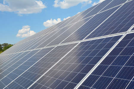 Photo pour A close-up on a solar panel with numerous solar modules and photovoltaic cells against blue sky with white clouds as a source of alternative, renewable green energy. - image libre de droit