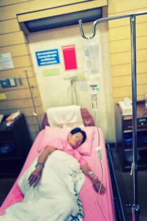 asia woman patient in the hospital bed saline intravenous (iv) drip