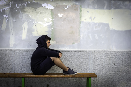 Photo pour Little boy sad sitting alone at school hides his face - image libre de droit