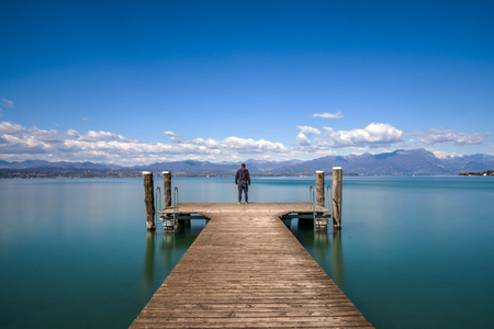 Photo pour Man standing on a jetty by tranquil lake Garda, Italy - image libre de droit