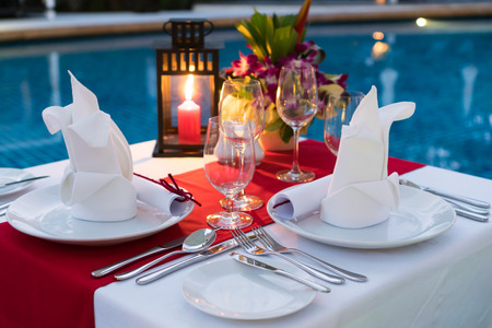 Foto de Romantic Candlelit Dinner Table; Poolside with Table Set. - Imagen libre de derechos