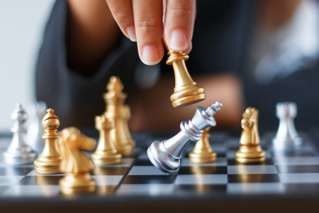 Photo pour Close up shot hand of business woman moving golden chess to defeat and kill silver king chess on white and black chess board for business challenge competition winner and loser concept, selective focus on king chess shallow depth of field - image libre de droit