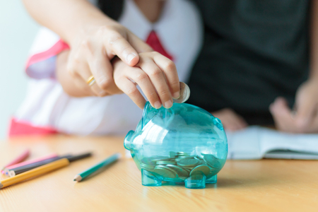 Photo pour Close up shot Asian little girl in Thai student kindergarten uniform with mother hand putting money coin into clear piggy bank saving money for education concept shallow depth of field select focus on pig - image libre de droit