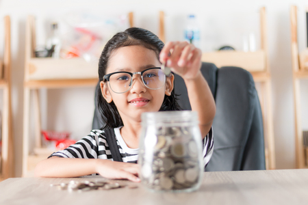 Photo pour Asian little girl in putting coin in to glass jar for saving money concept shallow depth of field select focus at the face - image libre de droit