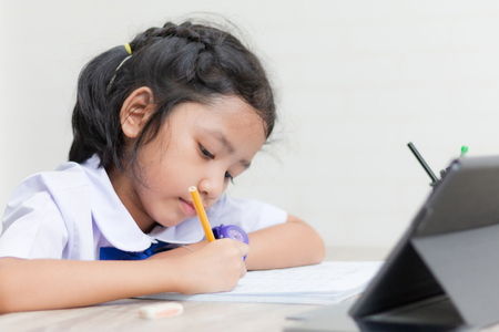 Photo pour Asian little girl in student uniform doing homework on wooden table with tablet select focus shallow depth of field - image libre de droit