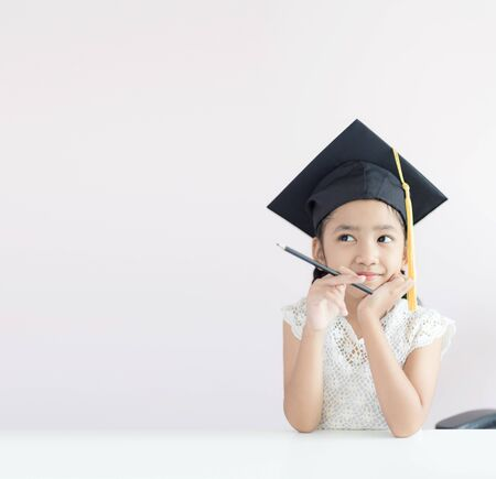 Photo pour Portrait little Asian girl is wearing graduate hat holding pencil sitting thinking something and smile with happiness select focus shallow depth of field with copy space for education concept - image libre de droit