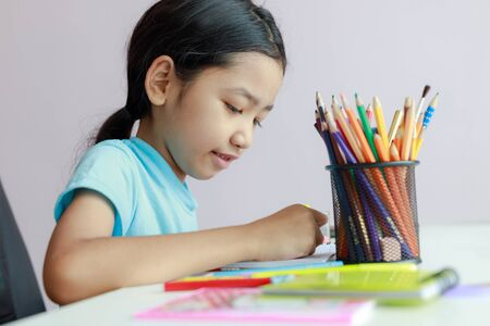 Photo pour Little asian girl putting doing homework use color pencil to draw on paper select focus shallow depth of field - image libre de droit