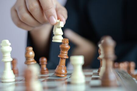 Photo for Close up shot hand of business woman playing the chess board to win by killing the king of opponent metaphor business competition winner and loser select focus shallow depth of field - Royalty Free Image