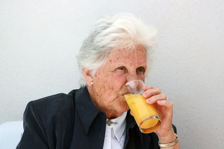 smart old lady drinking a cold glass of orange juice