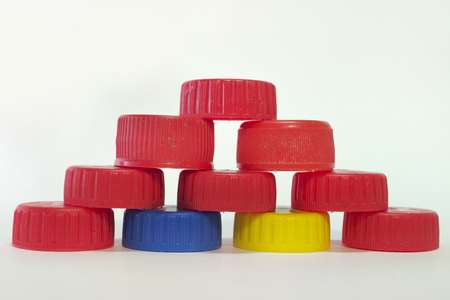 reds, blues, yellows striped caps from plastic bottles are collected in pyramid
