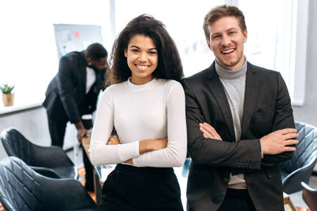 Photo pour Portrait of young adult business partners are standing with cross hands in modern office,. Happy confident multiethnic colleagues in formal wear looking at the camera, smiling, teamwork concept - image libre de droit