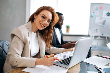 Photo pour Beautiful redhead woman is using laptop, working on project with colleagues. Happy female employee in stylish suit is sitting in modern office on business meeting, looking at the camera, smiling - image libre de droit