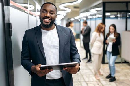Photo for Handsome successful businessman in formal stylish suit is standing in office hall, smiling. Attractive african american male employee looking at the camera, hold tablet in arms - Royalty Free Image