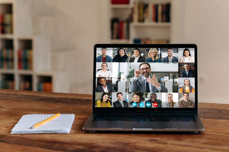 Foto de Virtual meeting.View at laptop screen with group of business people of different nationalities gathered from different parts of the world for communication and discussion business issues by video call - Imagen libre de derechos
