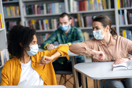 Photo pour Two female student friends wearing protective face masks greeting each other bumping elbows while sitting at university library, healthcare concept, precautions, new normal - image libre de droit