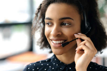 Photo for Close-up headshot of pleasant charming young african american curly haired woman in headset and stylish shirt, female call center worker or support operator, looking to the side, smiling friendly - Royalty Free Image