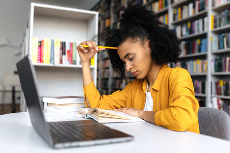 Photo pour Smart thoughtful concentrated mixed race student girl, sitting at table in university library, thinking about project or homework, gaining knowledge, preparing for exams, reading book - image libre de droit