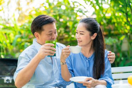 Foto de Happy mature couple talking together in green garden of home - Imagen libre de derechos