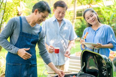 Photo pour Group of people picnic party in home garden with bbq food drinking and eating - image libre de droit
