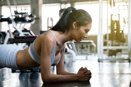 Photo for Sport fitness young girl doing plank position in gym, Work out women - Royalty Free Image