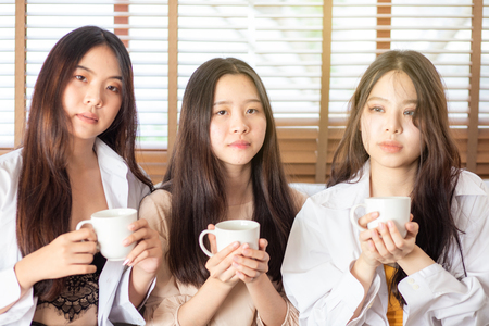 Photo for Group of asian girl having fun in home with coffee cup happy talking on couch at home - Royalty Free Image