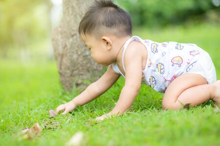 Photo for Cute smiling little asian boy crawling on green grass in city public park - Royalty Free Image