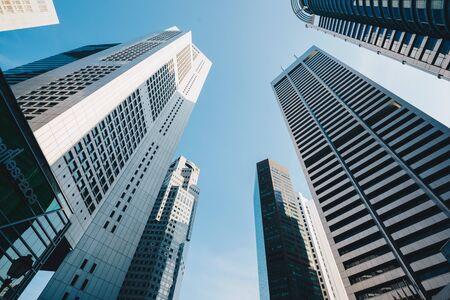 Photo pour Modern glass city buildings during sunny day. Low angle shot - image libre de droit