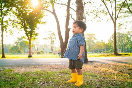 Photo pour Little asian boy try walking on green grass in public park sunset light, Baby boy in park - image libre de droit