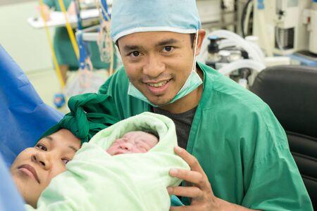 Foto de Newborn baby boy lying in hospital with father and mother - Imagen libre de derechos