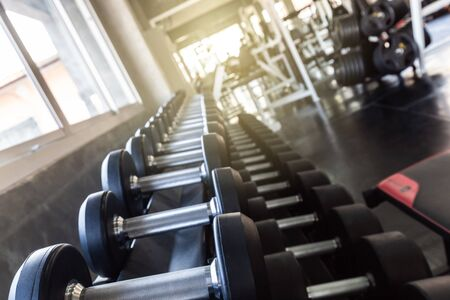Photo for Big dumbbell row on shelf in modern sport gym close up - Royalty Free Image
