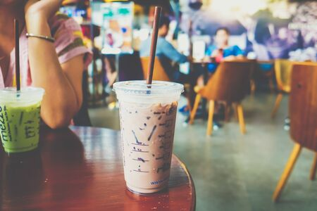 Photo pour Ice coffee cup on wooden table in modern cafe blurred people background - image libre de droit