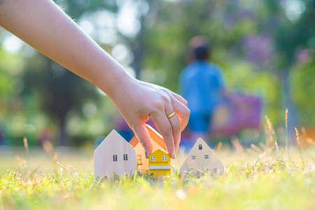 Foto de Hand choose wooden house on green grass saving concept for buying a home idea of investment funds - Imagen libre de derechos