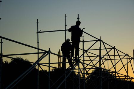 Photo pour Silhouettes of two builders constructing something in the evening - image libre de droit