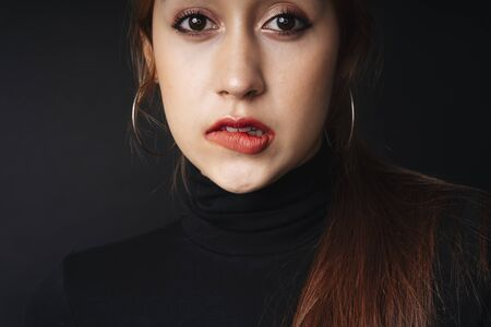 Photo pour Close up portrait of pretty beautiful young woman wearing black sweater isolate over dark background. Woman using red lipstick. Cosmetic concept. Bitting lips posing. - image libre de droit