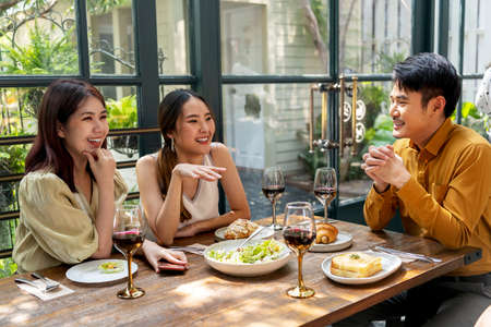 Photo pour Asian thai people enjoy having food together in the restaurant. People eating food at lunch time on table with wine. - image libre de droit
