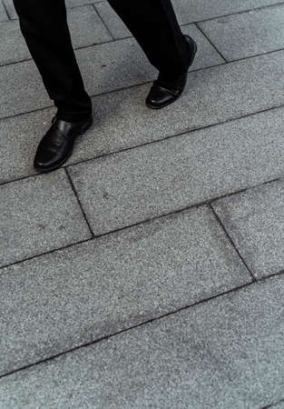 Photo for Low section shot of man wear cut shoes walking on pavement floor. - Royalty Free Image