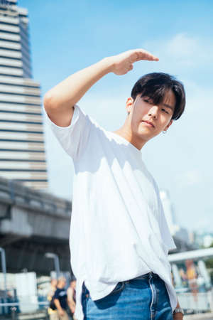 Photo pour Low angle shot of teenage guy in white t-shirt standing in the sunlight raise his hand protect his eyes with coll posture, vertical. - image libre de droit