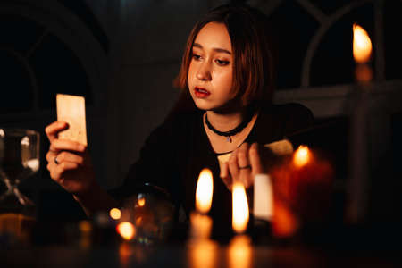 Beautiful young long hair woman fortune teller using tarot card to predict the future in dark room.