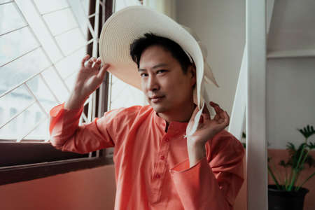 Photo pour Asian gay in orange mandarin collar try the white hat with ribbon and make the naughty eyes. - image libre de droit