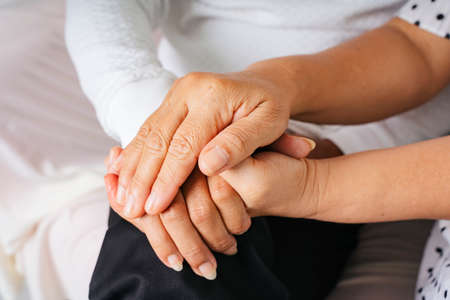 Photo pour Close up - Old elderly senior couple holding hands with care and promise. - image libre de droit