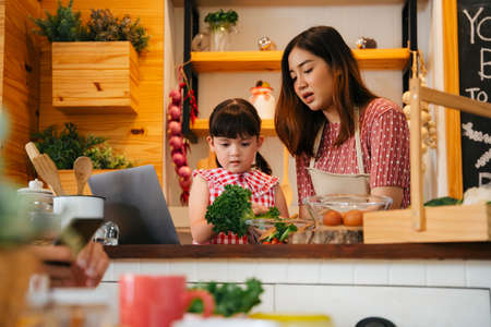 Photo pour Asian child and mother helping each other cooking in kitchen. People searching for food recipe on internet. - image libre de droit