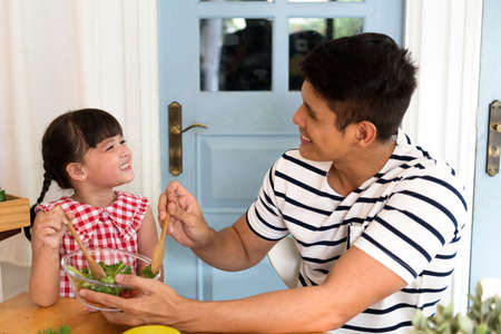 Photo pour Asian father and daughter enjoy eating food salad in kitchen together. - image libre de droit