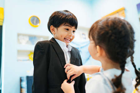 Photo for Cute sister helping her brother dress up formal suit at bedroom. - Royalty Free Image