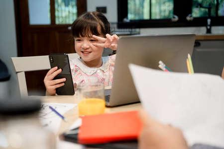 Photo pour Cute little girl selfie or vlogging with smartphone infront of laptop computer. - image libre de droit