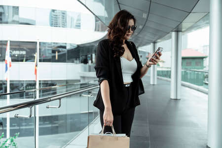 Photo pour Cool asian businesswoman wearing sunglasses holding smartphone and shopping bag standing in the city. - image libre de droit
