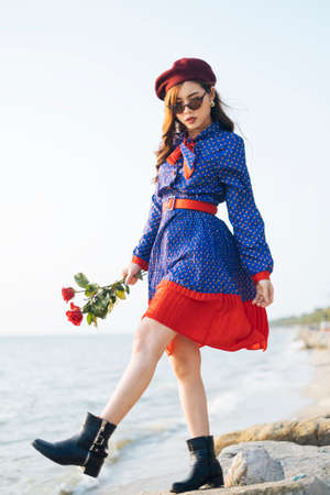 Photo pour Wavy brunette woman in blue and red retro dress walking on the rock at the beach and holf the roses. - image libre de droit